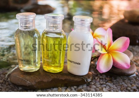Mini set of bubble bath and shower gel decorated in zen style with pebble rock and flower with relaxing mood - stock photo
