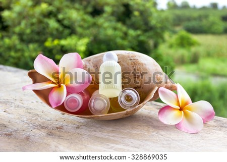 Mini set of bubble bath and shower gel in sea conch shell decorated with lovely flowers on fresh green nature view background - stock photo