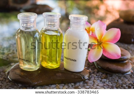 Mini set of bubble bath and shower gel in zen style decoration - stock photo