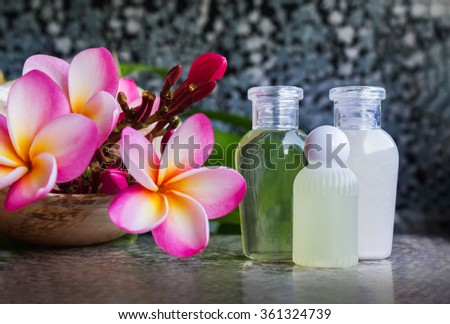 Mini set of bubble bath and shower gel liquid on marble table decorated with pink flower plumeria  - stock photo