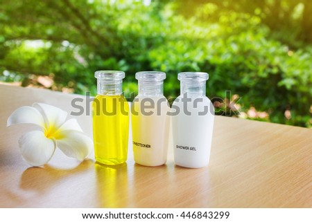 Mini set of bubble bath and shower gel liquid spa treatment with white flower plumeria or frangipani on wooden shelf with green tree bush nature background and relax mood - stock photo