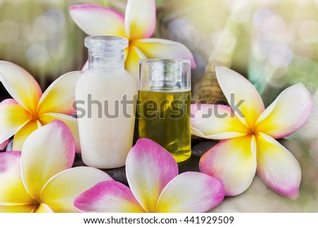 Mini set of bubble bath and shower gel liquid with pink flowers plumeria or frangipani on timber or log wooden background,shampoo and conditioner spa treatment in dreamy sweet bokeh  - stock photo