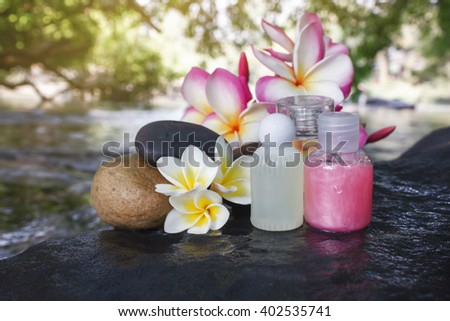 Mini set of bubble bath shower gel liquid with flowers and pebble on waterfall rock  with natural water relaxing feeling background and copy space - stock photo