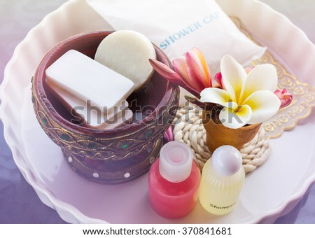 Mini set of shower bath soap, shampoo,conditioner decorated with flowers frangipani - stock photo