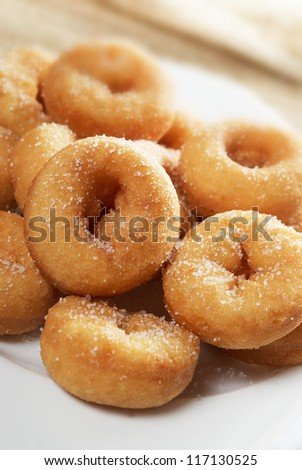 Mini sugar coated doughnuts piled on a white plate. Narrow dof - stock photo