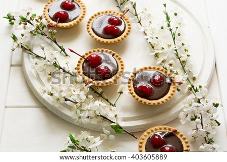 Mini tarts with chocolate and cherries decorated cherry blossom on white wooden background. Selective focus - stock photo