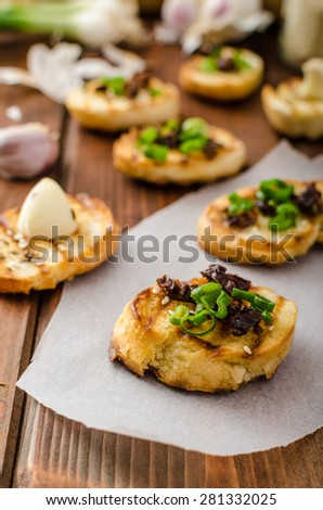 Mini toasts with garlic and dried tomato, sprinkled with herbs