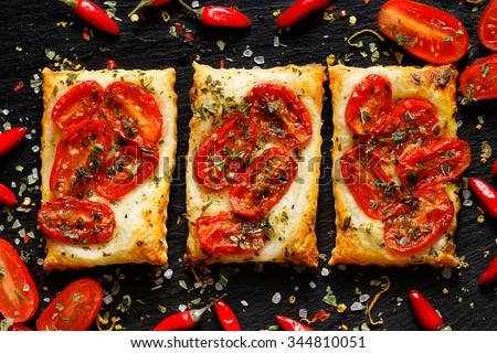 Mini tomato tarts with addition of aromatic herbs on dark background - stock photo