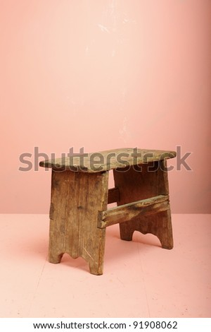 Mini Wood Stool over a pink background