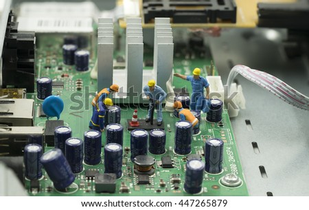 mini workers are working on mainboard to repair it - can use to display or montage on product or concept dig for fix - stock photo