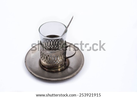 Miniature antique tea glass cup holder with a spoon - stock photo