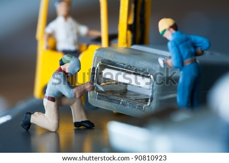 Miniature Artisans Doing Maintenance. A group of tiny miniature artisans working together to repair a cable connection in a teamwork concept - stock photo