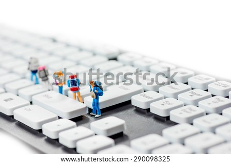 Miniature backpackers on top of the keyboard. Macro photo - stock photo