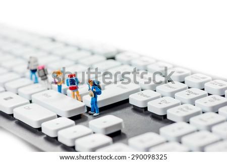 Miniature backpackers on top of the keyboard. Macro photo - stock photo