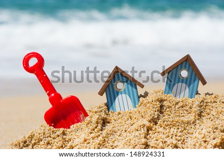 Miniature beach huts with red plastic shovel - stock photo
