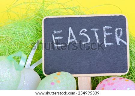 Miniature blackboard with easter eggs over yellow paper - stock photo