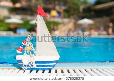 Miniature boat as toy at the swimming pool - stock photo