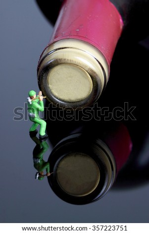 Miniature builder opening wine bottle