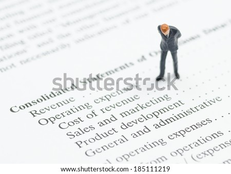 miniature business man stand on financial statement - stock photo