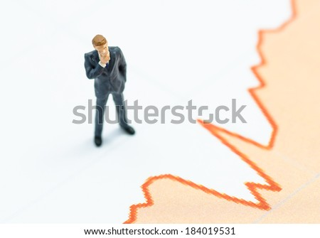 miniature business man stand on the graph - stock photo