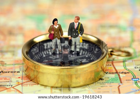 Miniature business travelers holding luggage and standing on a compass. The compass is on a map. - stock photo