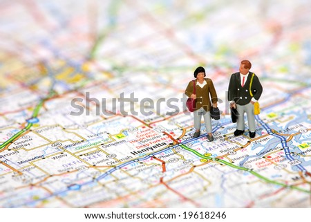 Miniature business travelers holding luggage and standing on a map. - stock photo