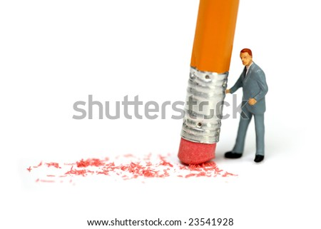 Miniature businessman holds a pencil and erases a mistake. Business, corporate, or accounting mistake concept. - stock photo