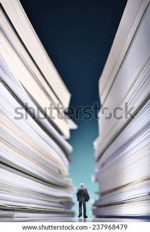 Miniature businessman lost into a huge pile of paperwork - stock photo