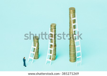 Miniature businessman observing three stacks of coins trying to choose the best investment. - stock photo