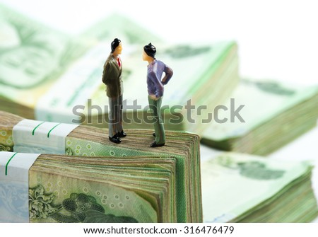 Miniature businessman on banknotes - stock photo
