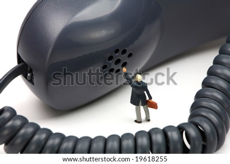 Miniature businessman stands in front of a gray telephone receiver waving for help. He feels small and helpless. IT support or customer service concept. - stock photo