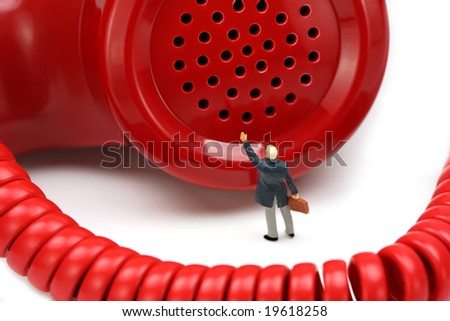 Miniature businessman stands in front of a red telephone receiver waving for help. He feels small and helpless. IT support or customer service concept. - stock photo