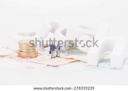 Miniature businessmen shaking hands with cash wooden letters background - stock photo