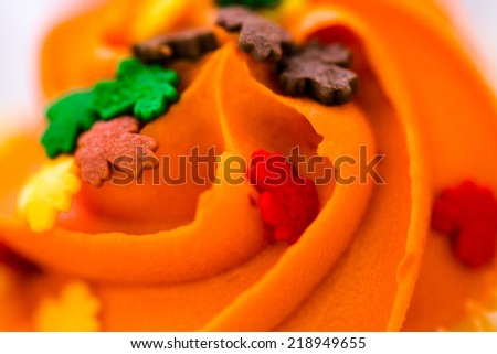 Miniature capcakes with yellow and orange icing and sprinkles. - stock photo