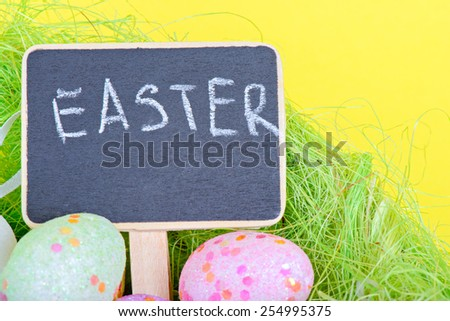 Miniature chalkboard with easter eggs over yellow paper - stock photo