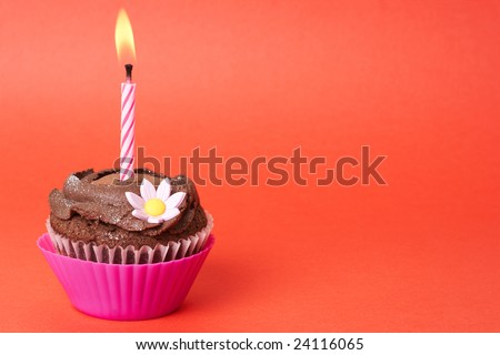 Miniature chocolate cupcake with icing, decorative flower and birthday candle on red background with copy space
