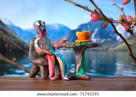 Miniature clay man in cafe with mountain lake view - stock photo