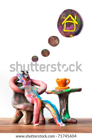 Miniature clay man sitting in cafe dreamin about estate - stock photo