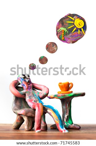 Miniature clay man sitting in cafe dreaming about exotic vacation - stock photo