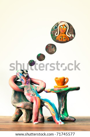 Miniature clay man sitting in cafe dreaming about women - stock photo