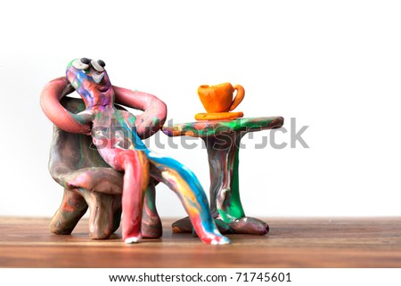 Miniature clay man sitting in cafe with cup of coffee and relaxing - stock photo