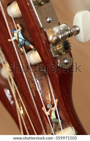 Miniature climber in action on a classic guitar