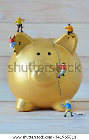 Miniature climbers climbing on gold piggy bank - stock photo