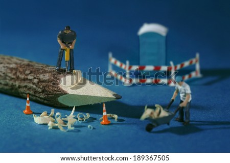 Miniature Construction Workers in Conceptual Imagery With Pencil - stock photo