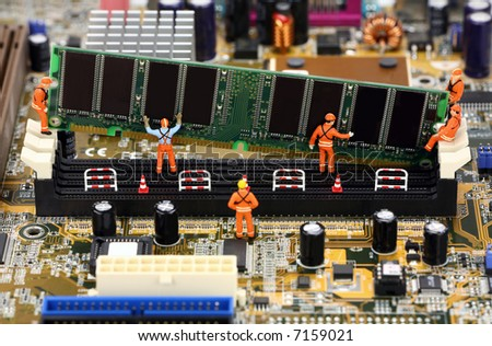 Miniature construction workers installing RAM memory on a computer motherboard. - stock photo