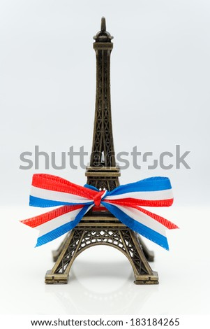 Miniature Eiffel Tower with a ribbon - stock photo
