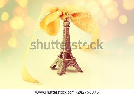 Miniature Eiffel-tower with defocused spot lights in background - stock photo