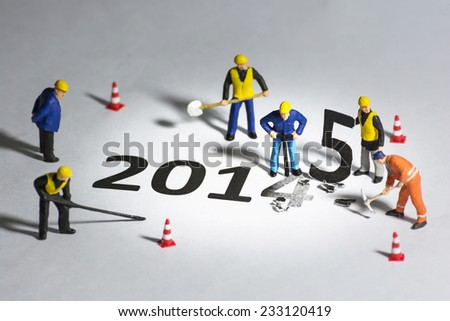 Miniature engineer or technician change represents the new year 2014 - 2015 - stock photo