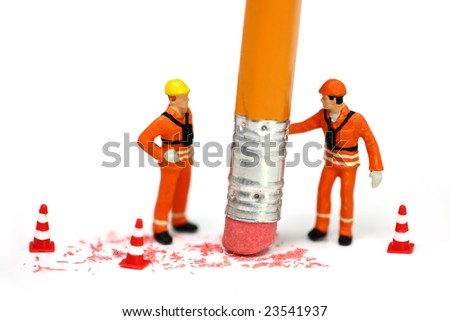 Miniature engineer or technician holds a pencil and erases a mistake while his associate watches. Engineering, construction, or technical mistake concept. - stock photo