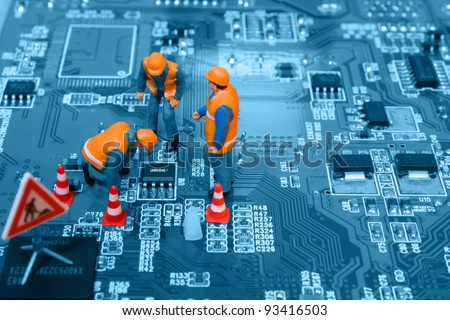 "Miniature engineers fixing error on chip of circuit board. Focus on word ""Warning"". Computer repair concept. - stock photo"